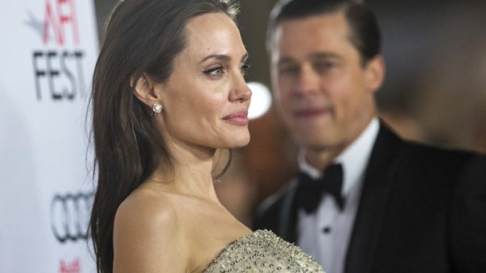 """Director and cast member Angelina Jolie poses, as her husband and co-star Brad Pitt stands nearby, at the premiere of """"By the Sea"""" during the opening night of AFI FEST 2015 in Hollywood, California November 5, 2015. The movie opens in the U.S. on November 13. REUTERS/Mario Anzuoni"""